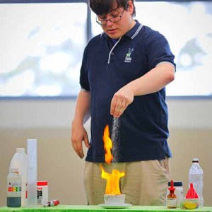 A presenter sprinkling salt into a yellow flame