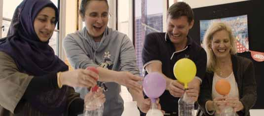 Teachers holding bottles with expanding balloons and smiling