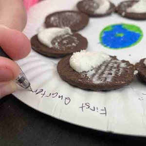 Writing the moon phases around the edge of paper plate with a pen