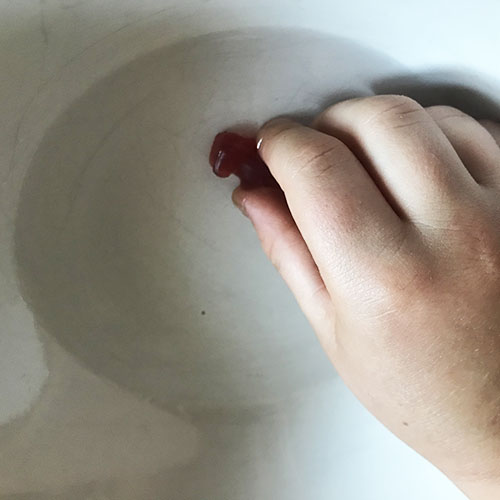 Placing a red gummy bear into a bowl