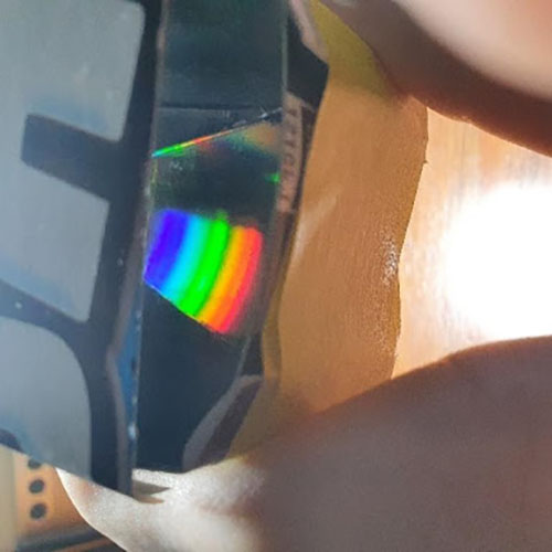 A rainbow pattern on a CD piece inside a spectrometer