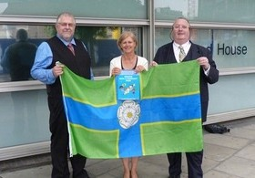 Charles Ashburner (Flag Institute Chief Executive), Helen Edwards (DCLG Director General), and Graham Bartram (Chief Vexillologist, Flag Institute) hold the North Riding flag.