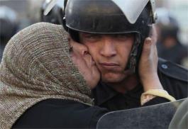 Une Égyptienne qui embrasse un policier qui ne veut pas tirer sur les manifestants