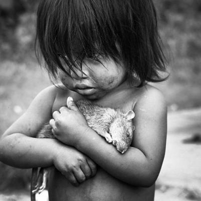 Une jeune Guarani avec un rat mort dans les bras