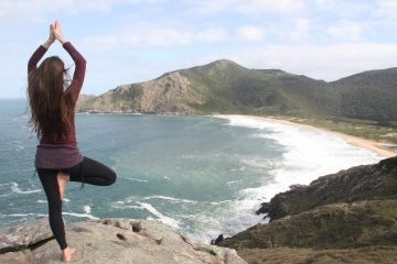 Lady doing standing balancing yoga asana near the beach