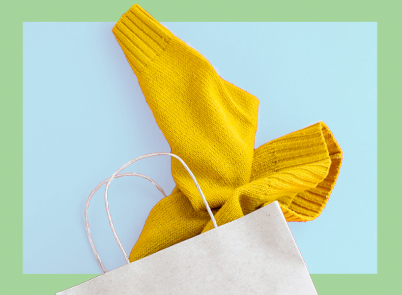 A yellow sweater sticking out of a white shopping bag