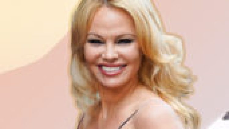 celebrity weddings 2020: Pamela Anderson smiles at the camera while wearing a black spaghetti strap tank top