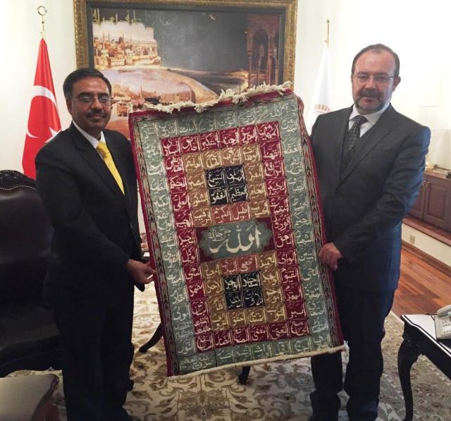 presenting a hand made Pakistani carpet