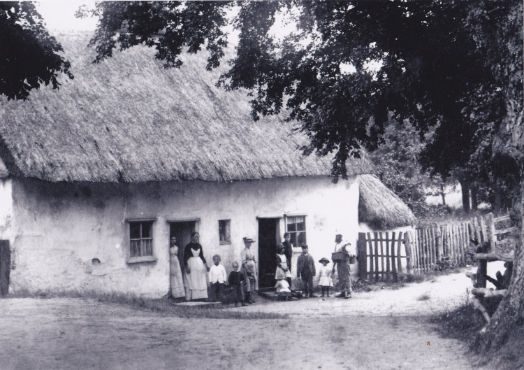 Black and white photo taken in 1899 showing two families standing outside Bridge Cottage