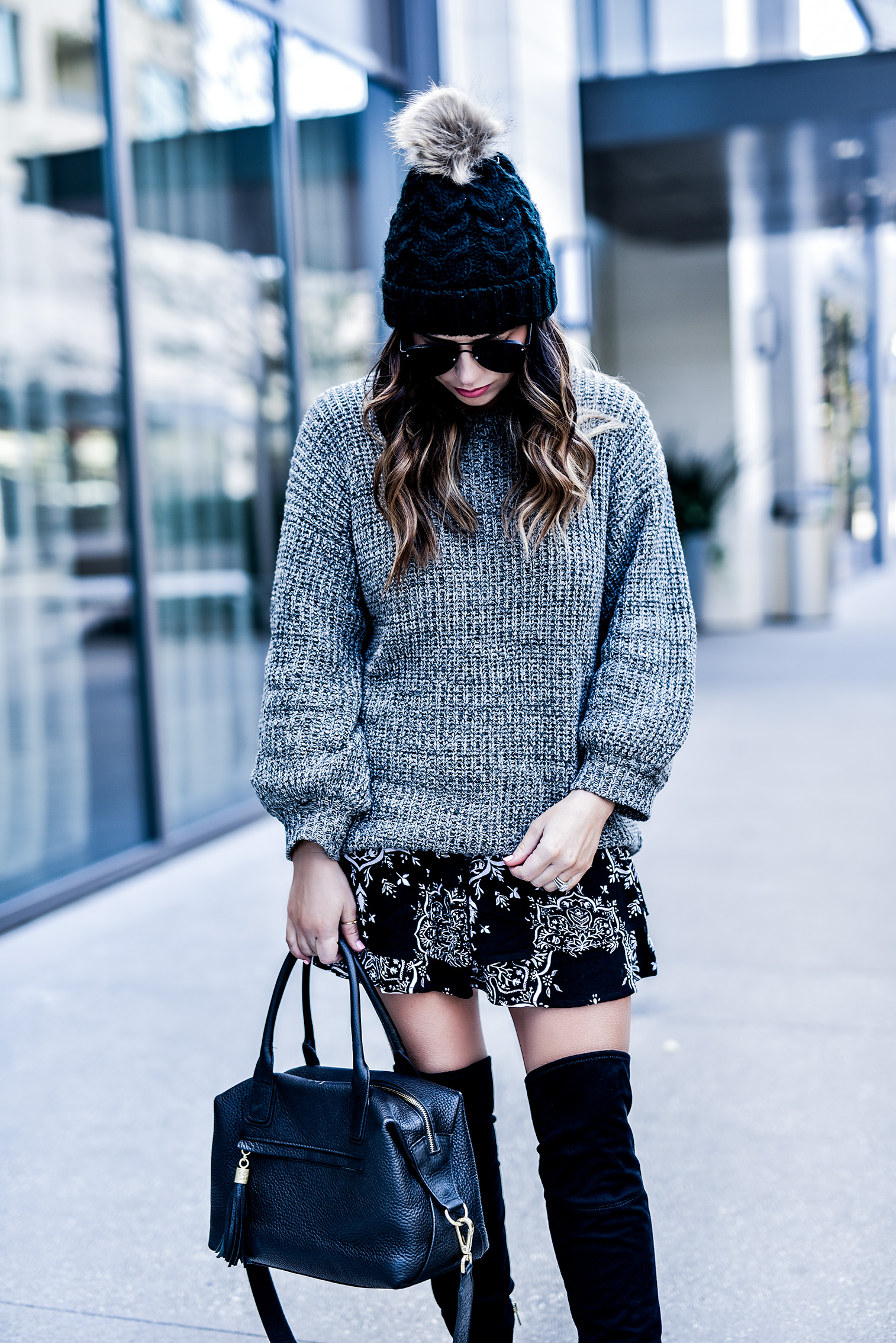 Flaunt and Center Houston style and fashion blogger Tiffany Jais wearing a chunky knit grey sweater by revolve and a printed skirt by revolve clothing, with a black pom pom beanie, and over the knee boots   Streetstyle