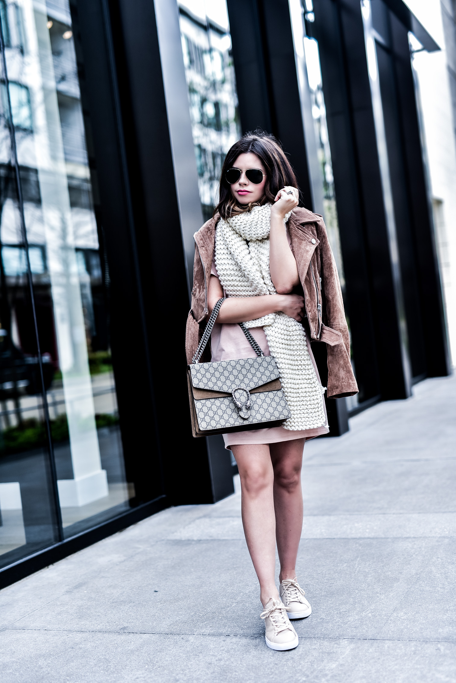 Houston fashion blogger wearing an asos pink dress and a blank nyc suede moto jacket, read up on how to concur effortless casual style by clicking this photo | Gucci Dionysus bag, chunky knit scarf, sneakers and a dress