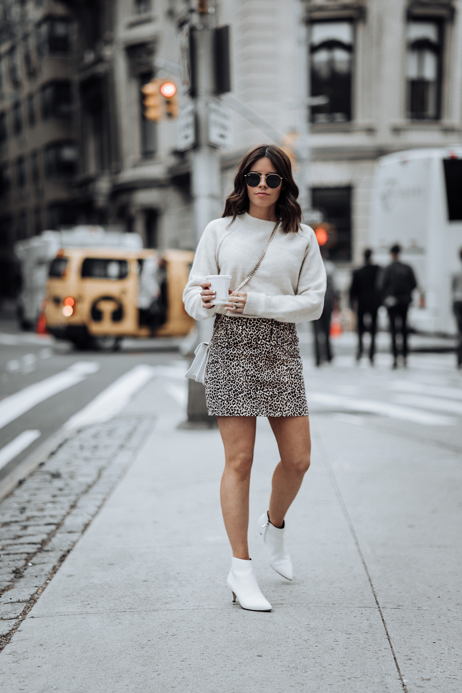 Revolve Leopard Mini Skirt | Sand color Sweater | J.W. Anderson Logo Purse | Similar white Ankle Boots here | #liketkit #ootd #style #blog #leopardskirt #streetstyle