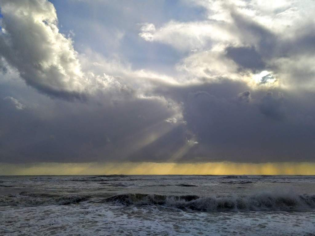 sun rays filtering through the clouds at the beach after a storm in Ostia
