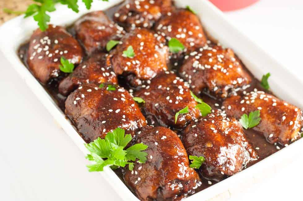 Slow Cooker Sticky Chicken thighs in a white serving dish garnished with cilantro and sesame seeds.
