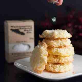 Sprinkling salt on Crispy Salted Coconut Cookies.