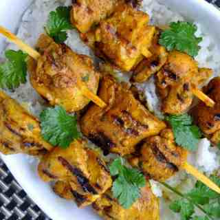 Grilled Turmeric Chicken Kabobs on skewers with rice