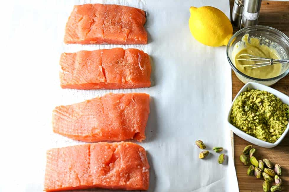 Raw salmon fillets, ready to spread with mustard, lemon and pistachios for Paleo Pistachio-Crusted Salmon