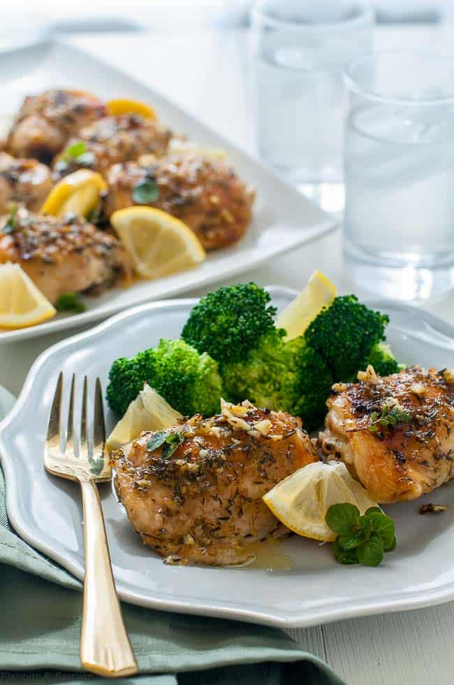 Easy Baked Lemon Chicken on a plate with steamed broccoli and lemon slices.