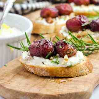 Side view of Roasted Grape and Goat Cheese Crostini on a serving board