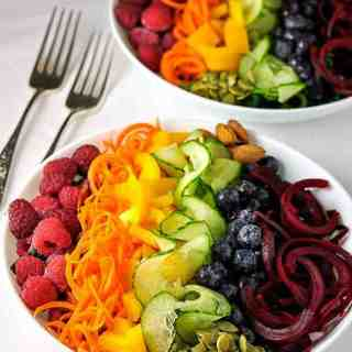 Rainbow Detox Salad. A rainbow or fruits and vegetables cut with a spiralizer and lined up in the colours of the rainbow in a bowl.