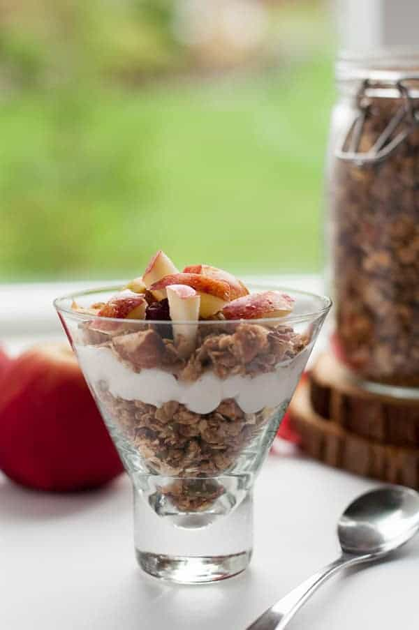 How to Make Apple Cinnamon Granola. Granola layered in a jar with yogurt and fresh apples.