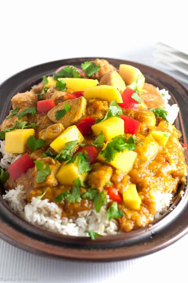 Slow Cooker or Instant Pot Thai Mango Chicken on rice on a stoneware platter.