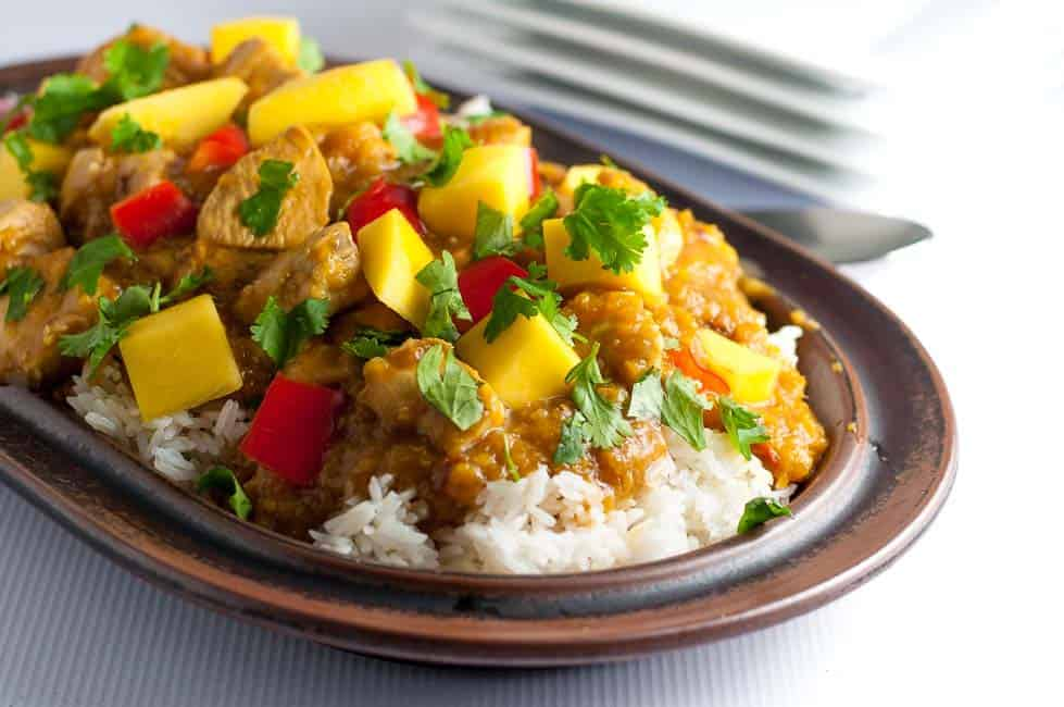 Slow Cooker Thai Mango Chicken on rice on a brown stoneware platter.