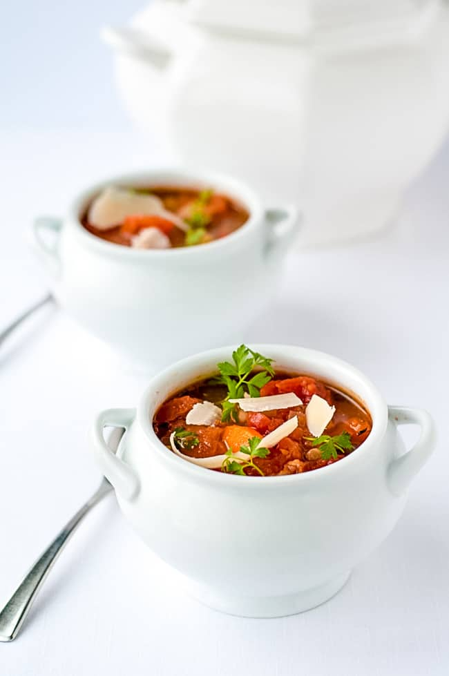 One-Pot Healthy and Hearty Tuscan Minestrone Soup in white soup tureens on a white background.
