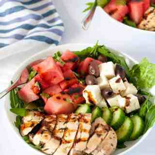 Skinny Greek Chicken Bowl with Watermelon and Feta, drizzled with a balsamic reduction. Succulent chicken marinated with lemon and herbs, sweet watermelon, feta cheese and Kalamata olives all drizzled with balsamic reduction.