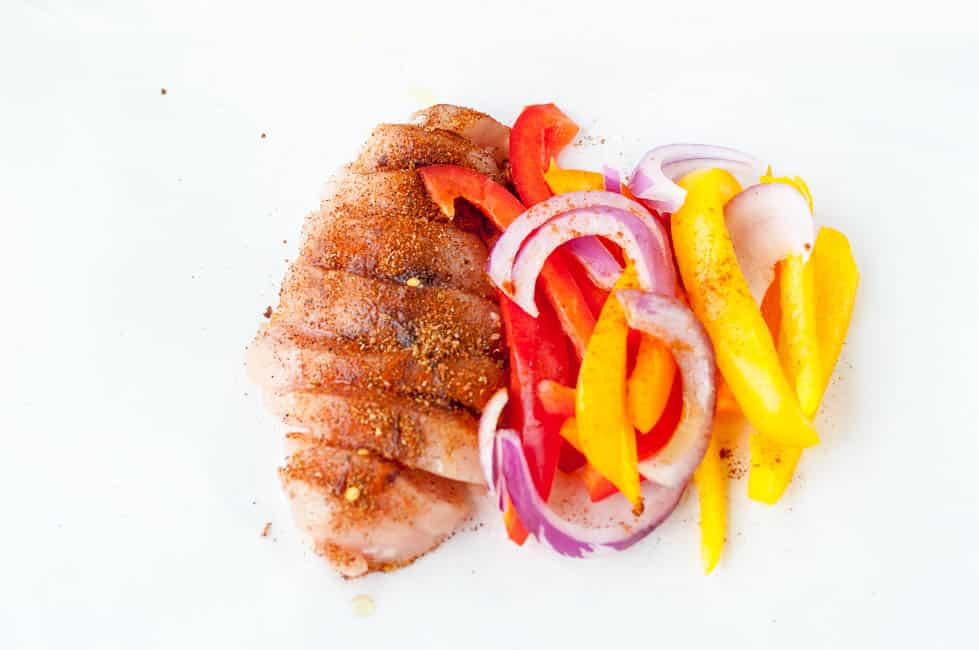 Sprinkle chicken with taco seasoning, add onions and bell peppers to Easy Chicken Fajitas in Foil Packets.