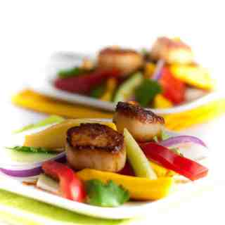 Seared Scallops with Mango Salad. Discover three simple steps to creating perfectly seared scallops and serve them on a colourful salad made with thinly sliced mango, red pepper, cucumber and red onion.