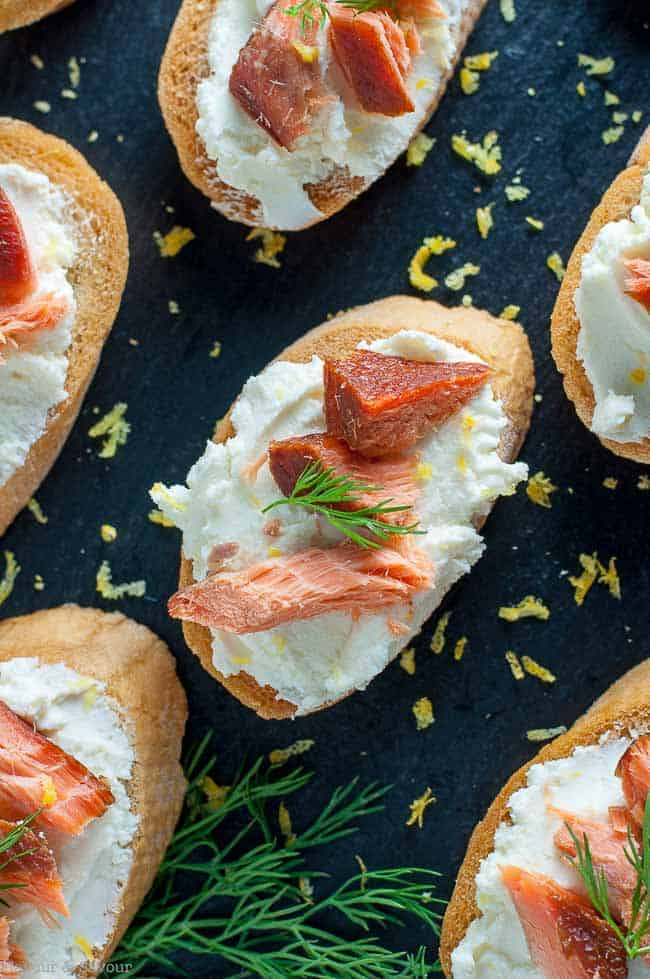 Try this Smoked Salmon Crostini with Whipped Goat Cheese made with slightly sweet honey-lemon goat cheese and smoked salmon when you need an easy appetizer. Great for game-day or tailgate parties. #smokedsalmon #wildsalmon #crostini #goatcheese #gameday #appetizer #partysnack