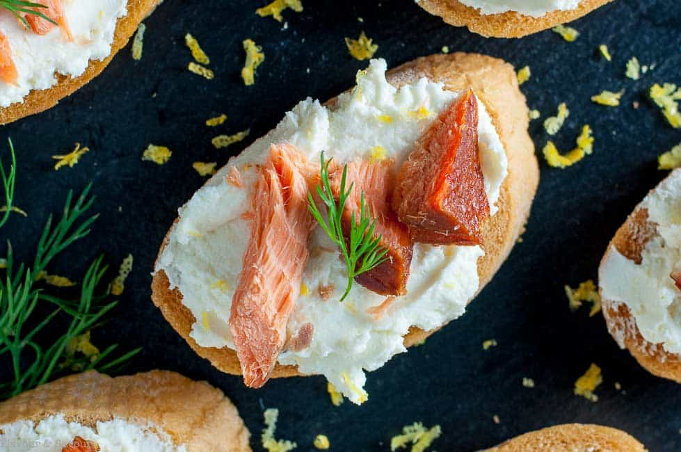 Close up view of Smoked Salmon Crostini with Whipped Honey Lemon Goat Cheese garnished with lemon zest and fresh dill.
