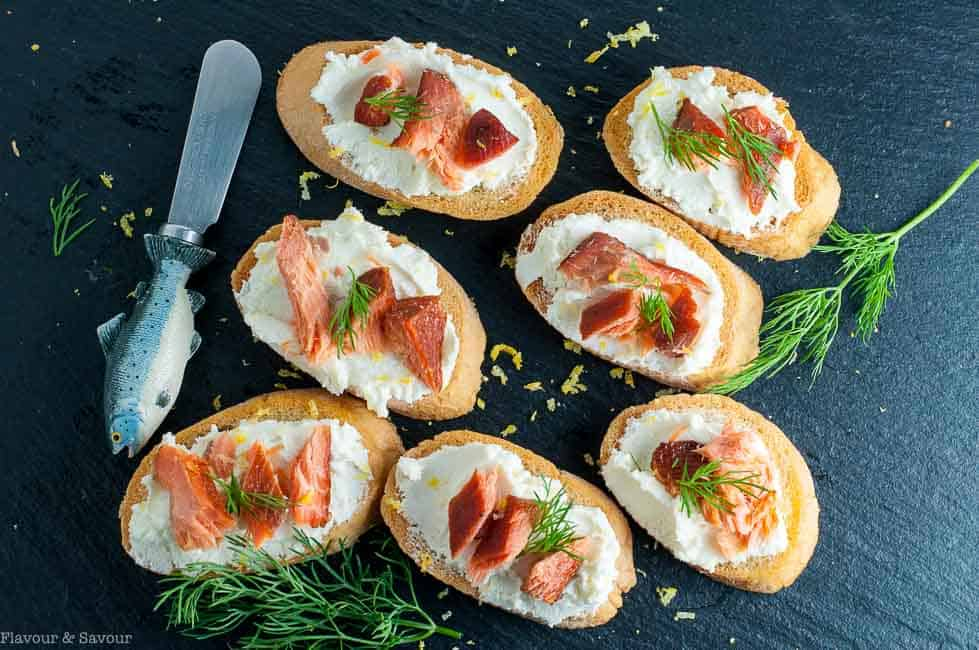 Smoked Salmon Crostini with Whipped Honey Lemon Goat Cheese on a slate tray.