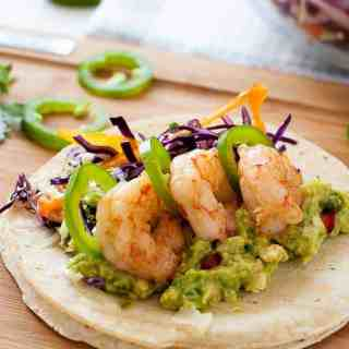 These Shrimp Tacos are loaded with zesty Tomatillo Guacamole and crunchy Cilantro Lime Slaw. They're topped with garlicky buttered shrimp, fresh jalapeño and a squeeze of lime.