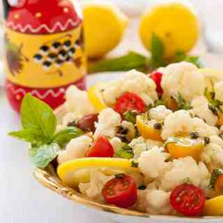 Cauliflower Lemon Basil Salad with toasted capers, fresh basil and cherry tomatoes in a bowl.