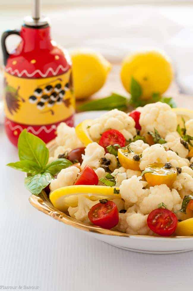Cauliflower Lemon Basil Salad in a bowl with oil dispenser and fresh lemons in background.