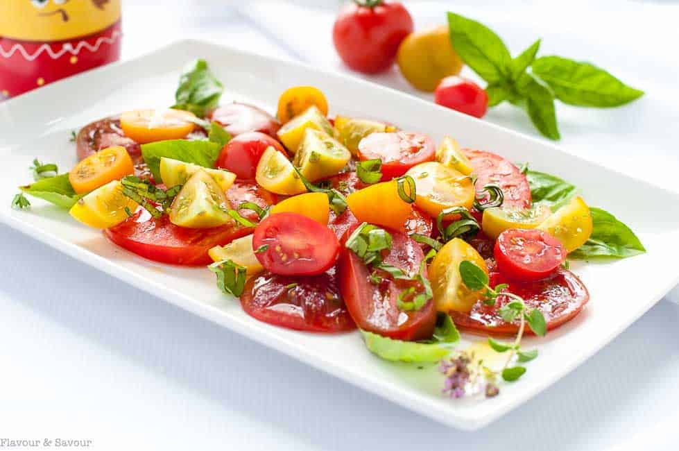 Heirloom Tomato Salad with Basil, Capers and Feta on a white rectangular serving platter.