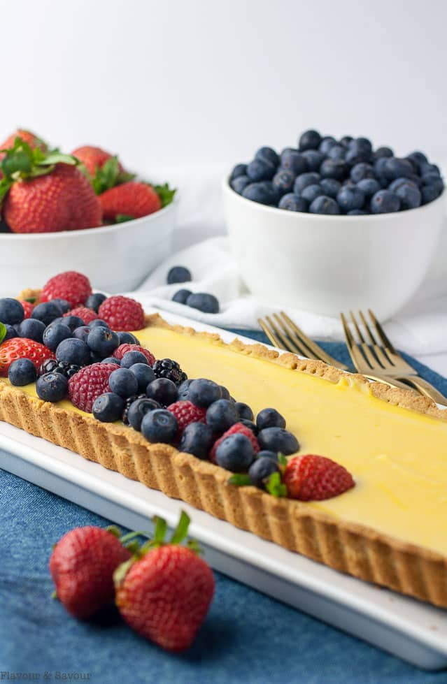 Side view of Gluten-Free Lemon Curd Tart with bowls of berries