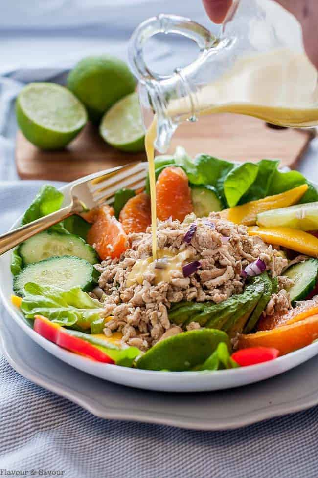Pouring Citrus Vinaigrette on Caribbean Shredded Jerk Chicken Salad_