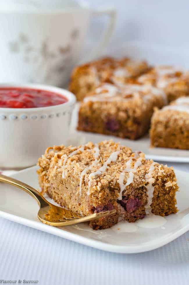 Paleo Strawberry Rhubarb Coffee Cake on a plate with a bowl of strawberry rhubarb compote