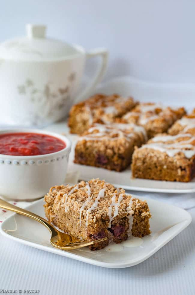 Paleo Strawberry Rhubarb Coffee Cake on a plate with a bowl of strawberry-rhubarb compote.