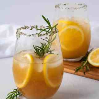 Two glasses of Pineapple Ginger Kombucha Cocktail garnished with a sprig of rosemary