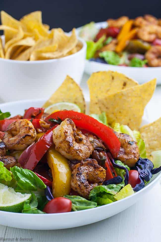 Shrimp Fajita Salad with Honey Lime Vinaigrette served with tortilla chips. Close up view