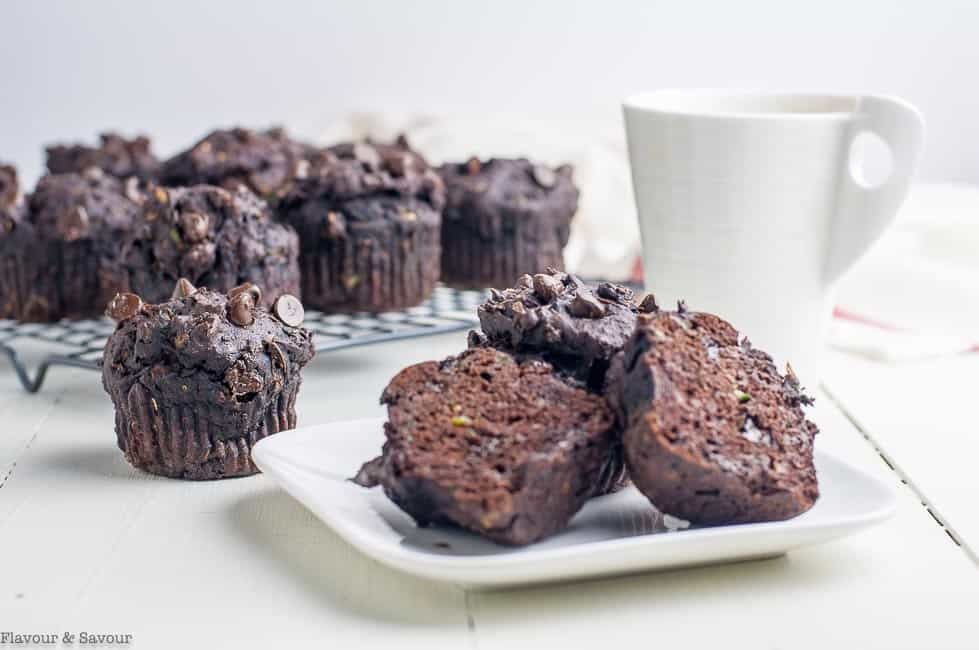 Gluten-Free Double Chocolate Zucchini Muffins on a white plate with a cup of coffee.
