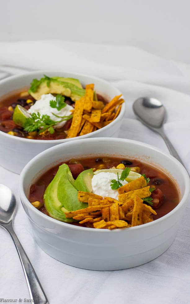 Slow Cooker vegan Texas Black Bean Soup garnished with avocado, lime and tortilla strips