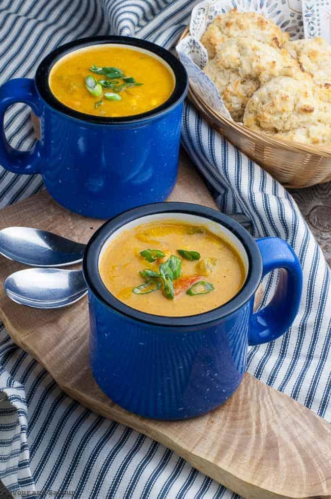 Hearty Vegan Sweet Potato Corn Chowder with turmeric in blue soup mugs