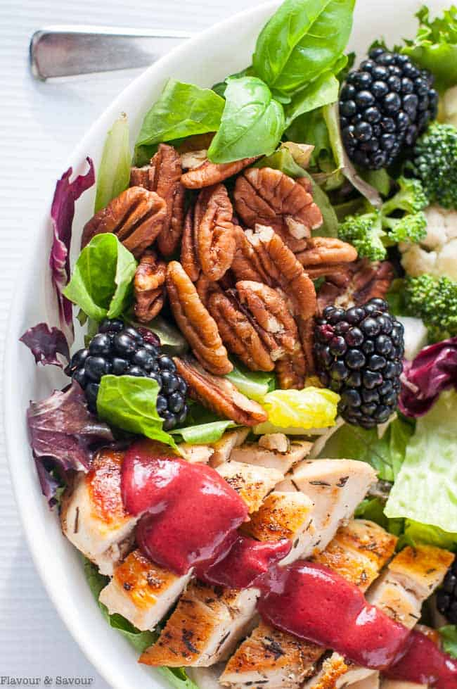 a bowl of chicken dinner salad with blackberry dressing
