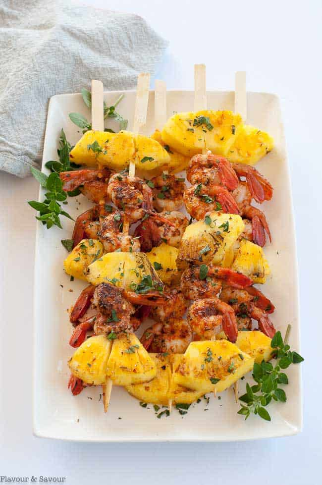 Grilled Cajun Prawn Kabobs skewered with pineapple on a platter