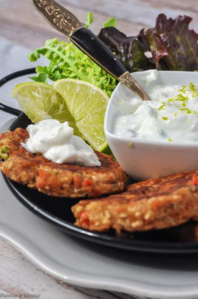 close up view of two salmon patties with lime yogurt dip